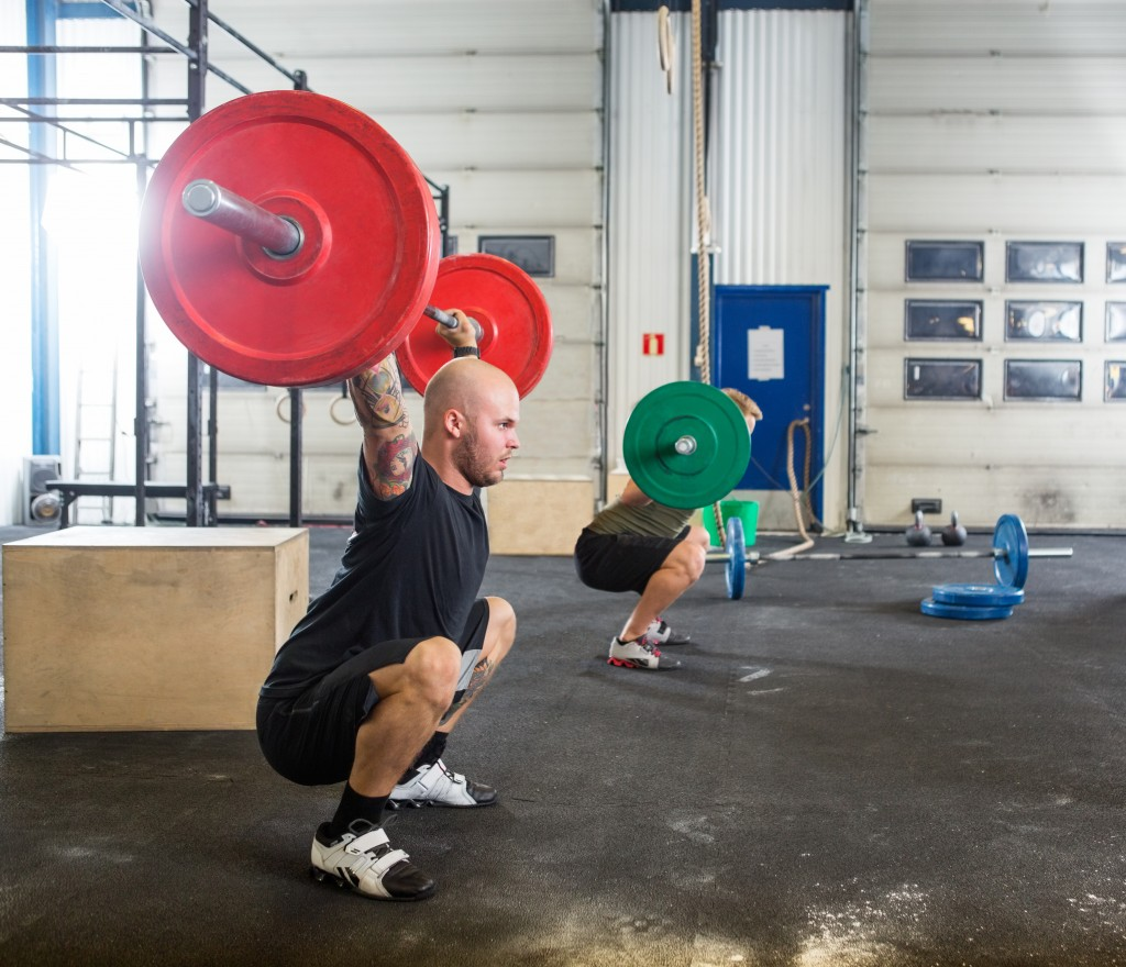 Two male atheletes exercising with barbells in crossfit box