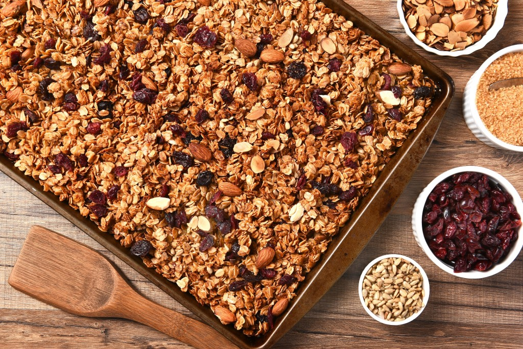 Horizontal overhead view of fresh homemade granola. Closeup of a baking sheet filled with the tasty, healthful food with containers of ingredients.
