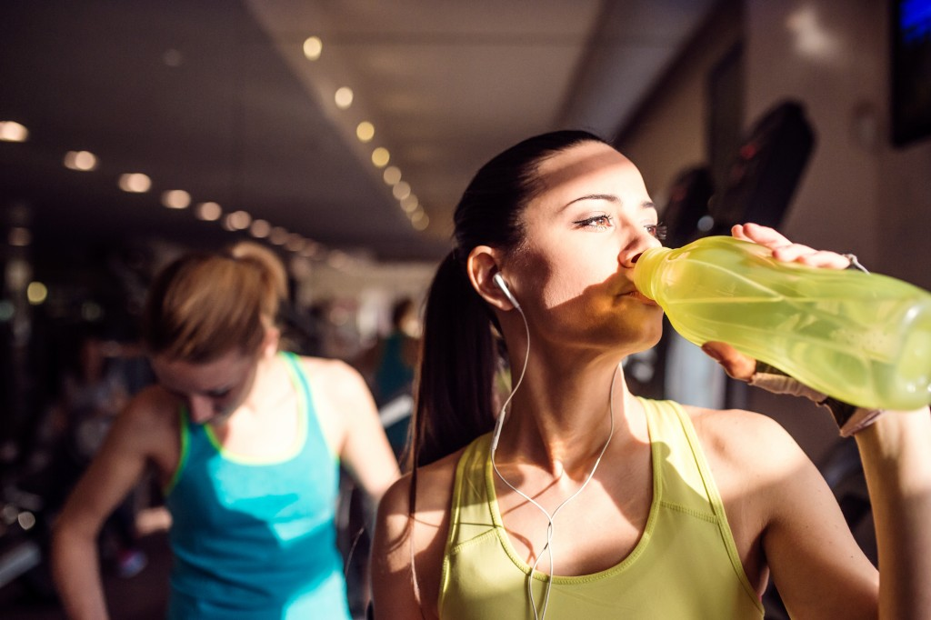 Attractive fit woman in gym drinking water from bottle, sunny day
