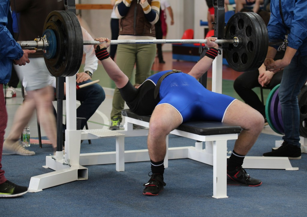 Competitions on powerlifting (weight lifting). Weightlifter pushes the barbell on the competition