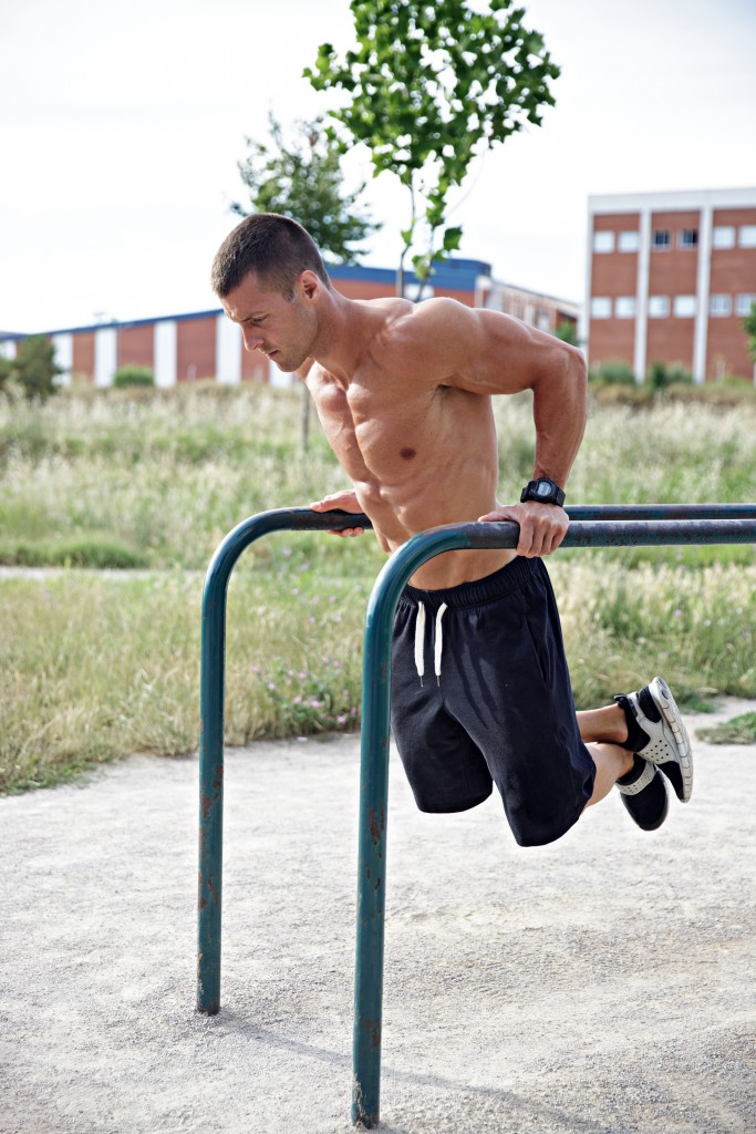 Young bodybulder doing dips