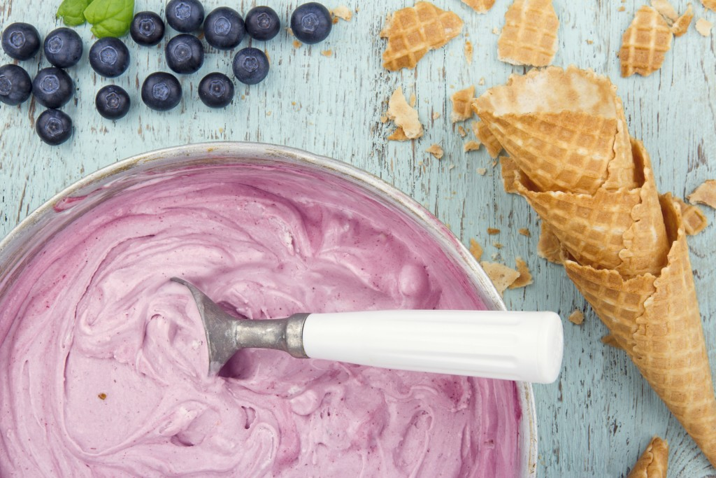 Homemade blueberry ice cream on vintage light blue wooden background