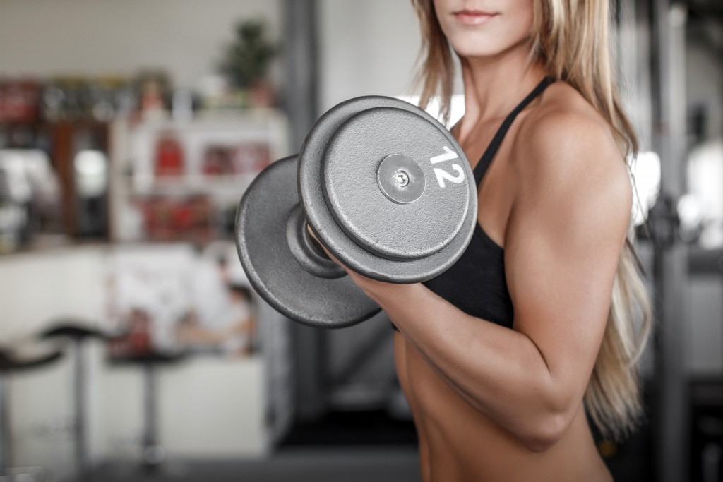 Woman workout with dumbbell in gym, biceps exercise closeup