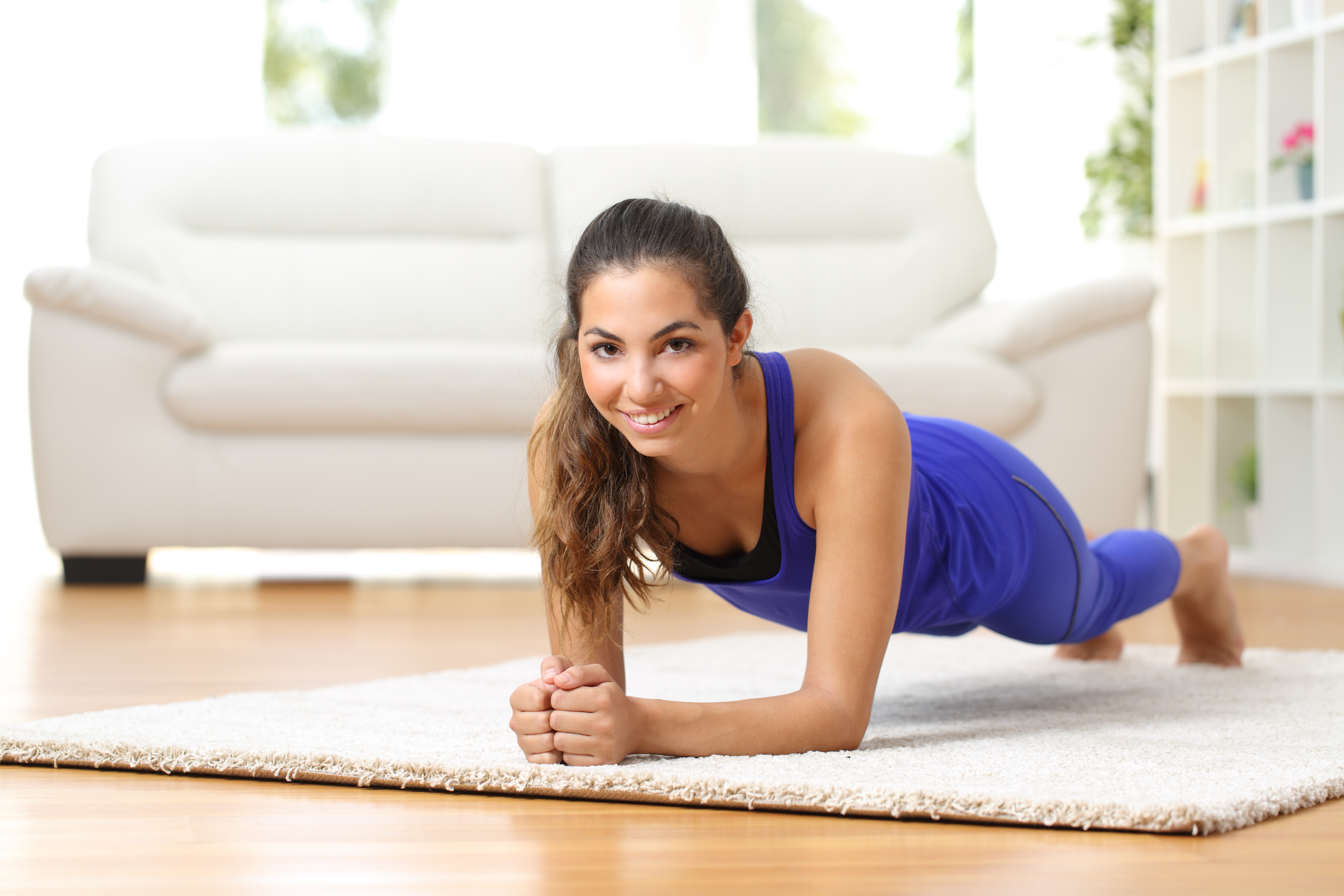 Fitness woman exercising on the floor at home and looking to the camera